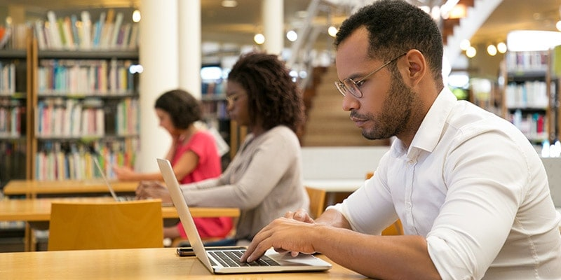 Young male student studying in library on laptop
